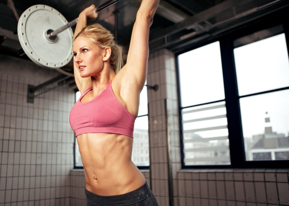 Woman doing shoulder press exercise with a weight bar inside a gym